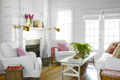 In the living room, walls painted Simply White by Benjamin Moore offer a bright and airy feel, while other elements (like orange pillows) add a pop of color.