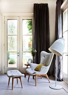 Seating area with grey linen armchair and foot pedestal, french doors, floor to ceiling black curtains and a large white floor lamp.