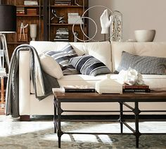 Neutral isn't boring! A beautiful clean-lined sofa sets the stage to layer graphic pillows in muted tones letting the collection of found objects take center stage.