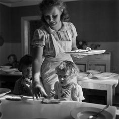 Nainen jakaa leipää lapsille   Heinonen Eino ? 1950—1959   Helsingin kaupunginmuseo   Nainen jakaa leipää lapsille. Elannon työntekijöiden lasten kesäsiirtola Sompasaaressa. -- negatiivi, nitraatti, mv