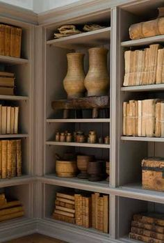 bookshelves mix of pottery and artifacts and books of same color