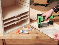 Gluing labels onto sandpaper shelves - so could use this for my craft room organization.