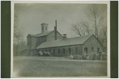 Paper mill site , probably J. D. Stowe & Son, Scitico (Enfield), about 1890, Description:Industrial masonry brick factory buildings on dirt road. Center three-story building has flat top cupola & 3-story projecting center addition on left. One-story building on right with pediment roof over door & large stack of logs. At right of door are what appear to be loosely piled drive belts. Barrels are at the left of a wood frame attached to building.