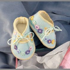 These little shoes are hand stitched in 100% pure wool felt. The colour is pale blue, lined with ivory wool felt. They have been given a vintage look with pastel coloured flowers hand stitched and trailing round each shoe. The have been embroidered with a light yellow cotton thread and finally tied with a pale blue velvet ribbon. The shoes are presented in a special gift box and will arrive nicely parcelled up with brown paper and string. The wool felt used to make my shoes meets all EU…