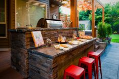Outdoor kitchen with bar top.  Contemporary Patio by Paradise Restored Landscaping & Exterior Design