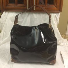 Michael Kors black patent leather hobo This is a magnificent Michael Kors black leather hobo with brown leather trim and strap. Gold studded detailing on the corners. Black signature lining. Large zipper pocket and four slip pockets. Great condition. Comes with care card. Michael Kors Bags Hobos