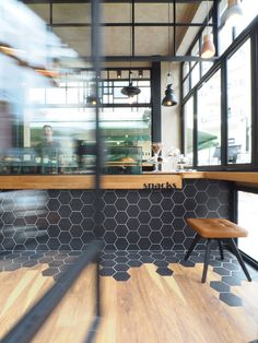 Inside this cafe, black hexagon tiles wrap from the counter to the floor where they meet wood laminate flooring.