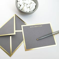 It is not happiness that brings gratitude, it is gratitude that brings happiness. - Flat gray card with gold foil border - Includes gray envelope with gold foil border - Includes ink test paper swatch