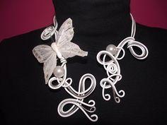 Participation #Sarah Carpentier  Pour réaliser ce collier, j'ai utilisé du fil d'alu blanc et de l'argenté irisé. J'ai travaillé avec 3 fils.  J'y ai mis des perles blanches et ajouté un joli papillon blanc brillant.  J'espère que ma création vous plaira...  Sarah.