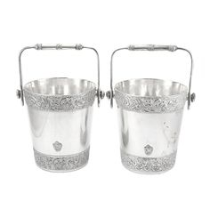 Companion Pair of Meriden Britannia Co. Silver Plated Ice Buckets  Each with a swing handle, decorated with cast and applied foliate bands. Height 8 5/8 inches, diameter 7 1/2 inches.