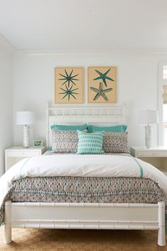 Beachside bedroom features a pair of teal starfish art over white bamboo bed dressed in turquoise and orange bedding and turquoise shams flanked by white mosaic table lamps atop Bungalow 5 Frances 2 Drawer Side Tables.