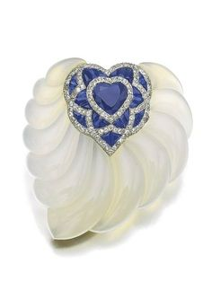 CHALCEDONY, SAPPHIRE AND DIAMOND BROOCH, SUZANNE BELPERRON, 1942 The heart-shaped sapphire framed with calibré-cut sapphires and circular-cut diamonds, inset to a carved chalcedony mount in the form of a leaf.