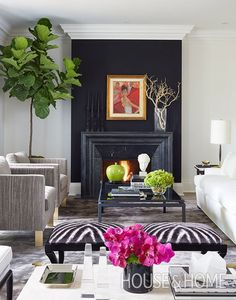 In designer Sloan Mauran's living room, a black wall melds into the carved Irish limestone fireplace surround, giving this focal point more presence. | Photographer: Virginia Macdonald
