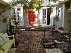 Bricked over patio.  Love the openings for flower beds and how homey the yard looks.