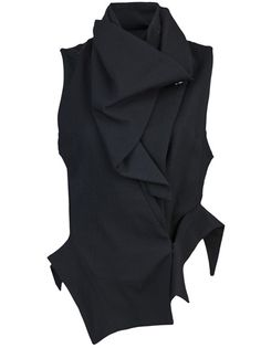 Drape neck vest in black from Ann Demeulemeester. This sleeveless vest features a drape neck with button fastening, a concealed asymmetrical front closure at the left side, front drape detail, and an asymmetrical hem with short sides.