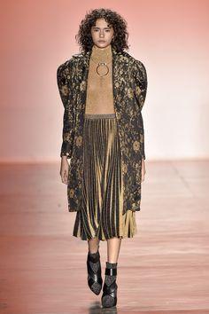 Overcoat dourado e preto, com estampa floral, tecnologia de fios flutuantes, blusa gola alta de lurex dourada e saia plissada. Foto: Agencia Fotosite