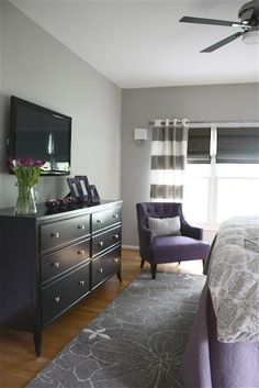 Love the matte black furniture, gray walls (is that woodsmoke?) and rug! Needs moulding. Use yellow instead of purple for a bright pick-me-up!