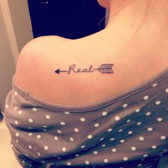 """Artifact #3 This photo shows a fan who has gotten a tattoo reprsenting something that was said in The Hunger Games. The character Peeta Mellark asked Katniss Everdeen, """"You love me? Real or not real."""" Katniss answered """"Real"""". This quote became very popular and fans started to get shirts and even tattoos to relate to this quote.:"""