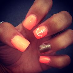 orange nails with gold on ring finger and anchor on middle finger