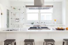 Kelly Deck - White kitchen featuring stainless steel hood hovering over island with integrated gas cooktop and white quartz countertops lined with Tolix Stools across from white base cabinets framing stainless steel apron sink flanked by wall adorned with stacked wire hangers holding artwork and schoolwork adjacent to walk-in pantry with seeded glass door.