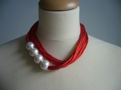 Red necklace with white pearls
