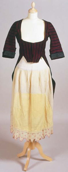 Flannel 'betgwn' or bedgown featuring red and black vertical stripes. Sleeves half-lined with black taffeta. Turned-back cuffs. The bodice appears to have been constructed from scraps of cloth. Two decorative covered buttons have been used at the back of waistband. The cream flannel petticoat or underskirt which also appears features hand-embroidered pink flowers and scalloped edge. It has been extensively repaired by its owner.