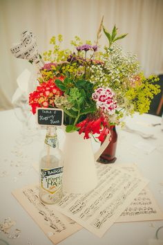 Sheet music centre piece with heart stick in Jugs of bright wild flowers - Lucy G Photography - A marquee wedding with a lace gown and colour pop theme with mix and match centrepieces.