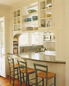 A sweep of curved stone, something you would never have seen in the olden days, makes a pleasing, dramatic countertop for a pass-through. White, traditional cabinets and rush-seated stools add warmth I like the curve bcuz its easier to see / talk with others