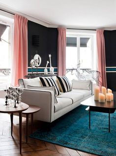 A striking Parisian living room with many candles on coffee table, black and white striped pillows on a neutral sofa, and pale pink curtains