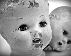 two doll heads, vintage black and white doll head art photo, cracked faces and staring doll eyes, creepy or cute antique dolls
