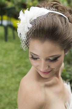Tiara Gisele fica linda com penteados de noivas como coque ou cabelo meio solto, é feito com um lírio estilizado em cetim e organza, com pistilos de vidrilho e delicado voilette de R$ 310,00 por R$248,00.