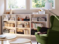 A basement living room with three low BILLY bookcases in white and a STRANDMON wing chair in green