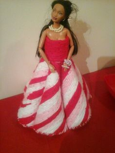 A doll i dtessed red white and pink yarn