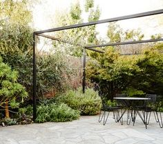 Brian and Trish Perkins' mixed low maintenance shrub and perennial planting soften the boundaries of the slate paved courtyard. Tio Collection dining table and chairs by Mass Productions. Photo by Annette O'Brien. via The Design Files. Diy Pergola, Building A Pergola, Pergola Swing, Wooden Pergola, Outdoor Pergola, Pergola Shade, Pergola Ideas, Outdoor Patios, Cheap Pergola