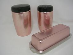 Three items by West Bend in a pinkish aluminum color. Butter dish high Salt high All in okay condition--some scratching.