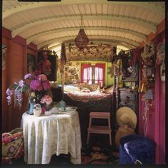 Saint-Rémy-de-Provence - Inside a Gypsy caravan with vibrant green and pink painted walls. The caravan has a living area and a small set of steps leads up to a bedroom area.