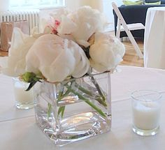 This is a cube vase floral arrangement that features white peonies.  See our entire selection at www.starflor.com.  To purchase any of our floral selections, as gifts or décor, please call us at 800.520.8999 or visit our e-commerce portal at www.Starbrightnyc.com. This composition of flowers is generally available for same day delivery in New York City (NYC). SQ135