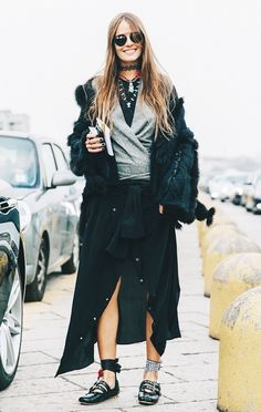 A gray self-tie sweater is worn with a black button down skirt, black fur jacket, layered choker necklaces, and Miu Miu ballet flats.