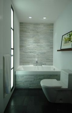 Slate cladded bath panel with main feature above. Honed Black slate floor.
