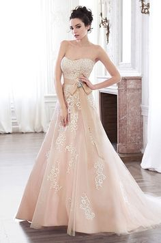 Floral lace adorns this blush color tulle A-line wedding dress. Maggie Sottero, Spring 2015