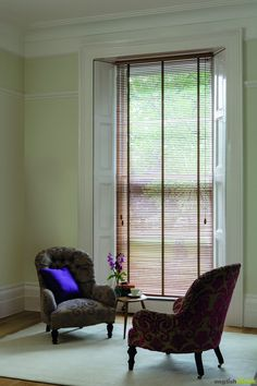 Luxury light oak wooden venetian blind, pale green room, traditional embroidered chairs.