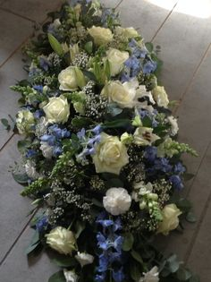 and white coffin spray, blue delphinium, white roses, white lily's, casket spray . Funeral Floral Arrangements, Flower Arrangements, Dad Funeral Flowers, Funeral Caskets, Casket Flowers, Funeral Sprays, Casket Sprays, Memorial Flowers, Cemetery Flowers