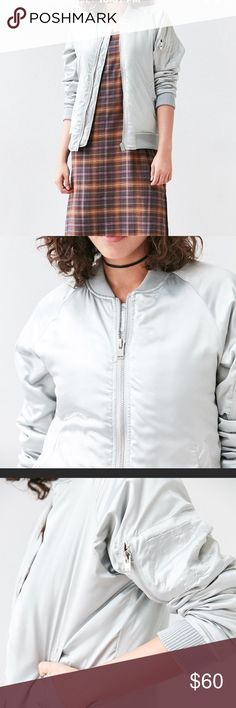 """❤️NWT UNIF silver satin bomber by Urban Outfitters Rizzo-approved satin bomber jacket exclusively for UO by UNIF. In a slouchy fit flanked with snap-button pockets and trimmed with stretchy ribbed knit hems all over. Finished with a mini zip pocket at the arm. - Polyester - Dry clean - Imported - Model in Silver is 5'11"""" and wearing size Small - Measurements taken from size Medium - Chest: 44"""" - Length: 26"""" Urban Outfitters Jackets & Coats"""