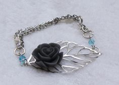 Delicate silver filigree leaf bracelet with a grey polymer clay rose with aqua swarovski crystals with 2 strands of silver chains. $18.00, via Etsy.