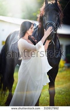 Fashionable lady with white bridal dress near brown horse. Beautiful young woman in a long dress posing with a friendly black horse. Attractive elegant female with horse, close-up photo
