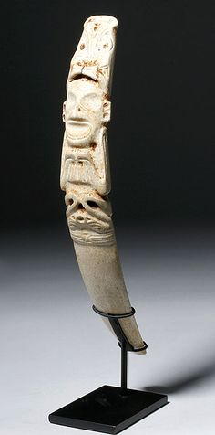 Caribbean, probably Dominican Republic, Puerto Rico, or Jamaica, Taino, ca. 1000 to 1500 CE.  A special ceremonial implement for the Cohoba ritual, boldly carved with a skeletal Zemi figure (a being housing a god, spirit, or ancestor), its form meticulously delineated (notice the spine and ribcage visible on the backside) donning a tall, elaborately incised headdress and holding its hands underneath its open mouth, all hand-carved from manatee bone that is the process of fossilizing and…