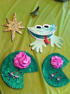 Princess And the Frog family movie night crafts. Lily pads, frogs and the evening star. The evening star is just made from a piece of a cardboard box. I cut it out, wrapped with aluminum foil, covered with Mod Podge and let my daughter glitter away. We also made fireflies in a jar (cut open a glow stick an put in a empty baby food glass jar with some fine glitter).