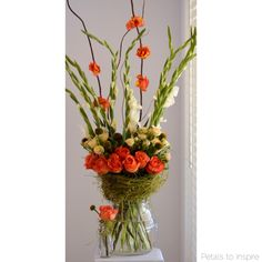 Tall modern vase arrangement featuring orange roses, white gladioli's, clustar roses and dodder vine - tropical & lush by Petals to Inspire