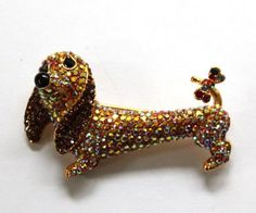 THIS IS NO INFO ON THE PRETTY PIN THAT HAS JEWELS AND A BOW ON THIS DACHSHUND'S TAIL.