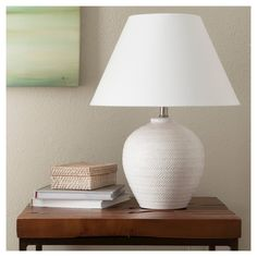 Rich in detail and pleasing in shape, the Threshold Carved Ceramic Table Lamp brings incandescent style to your living room or bedroom. Combining a rounded cream colored body carved with herringbone pattern and silver hardware, this lamp is capped off with a white empire lampshade for complete elegance. Pair with a wide variety of furniture styles for a versatile indoor lighting option you'll love.
